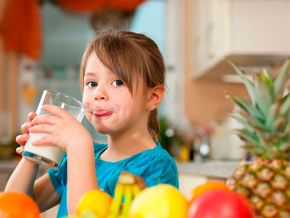 Little girl enjoying a glass of milk, surrounded by colorful fruits